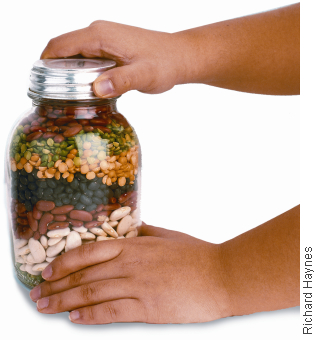 Photograph of hands holding jar with screw top and filled with layers of beans.